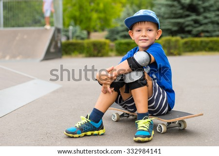 Handsome little boy sitting on his skateboard in his safety gear smiling at the camera as he takes a break at the skate park - stock photo