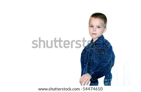 Handsome little boy stands besides a white picket fence on an all white background.  He is dressed in a denim jacket and overalls.  His look is solemn and his blue eyes match the blue of his jacket. - stock photo