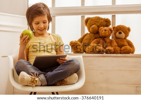 Handsome little boy using a tablet, holding and apple and smiling while sitting on a chair near the window - stock photo