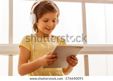 Handsome little boy using tablet and listening to music while sitting near the window - stock photo