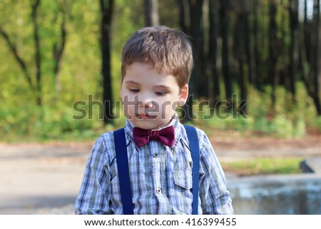 Handsome little boy with bow tie looks down in sunny green park  - stock photo