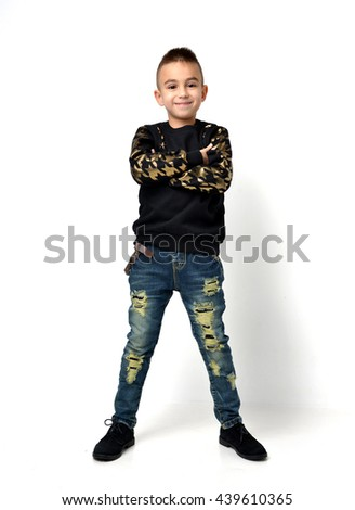 Handsome little school boy standing posing in blue fashion jeans and modern army sweatshirt  happy smiling on white background - stock photo
