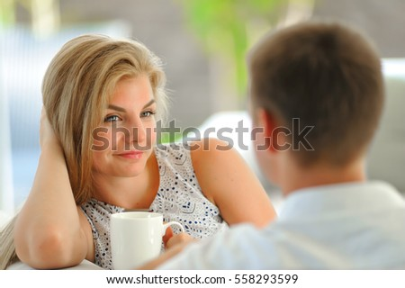 Handsome long haired young blonde woman sitting on a couch propped her head with one hand and holding a mug of delicious tea in another hand, in love looking at her husband