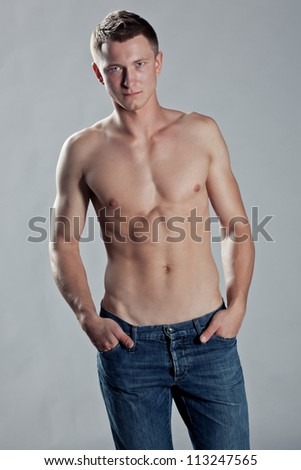 Handsome macho man posing shirtless to display his physique and muscles ,holding his fingers in pockets - stock photo