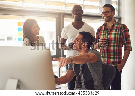 Handsome male adult pointing at something on his computer for a group of laughing male and female casually dressed friends holding drinks - stock photo