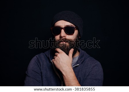 Handsome male big beard in glasses and hat, studio shot on black background, looking directly at the camera