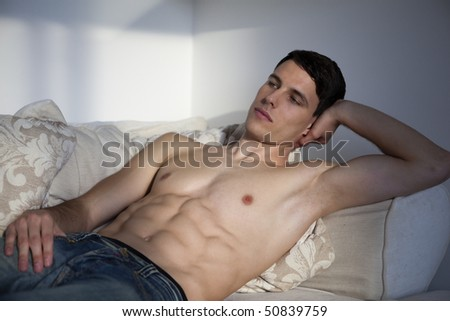 Handsome male body. Young man is lying on the white sofa.