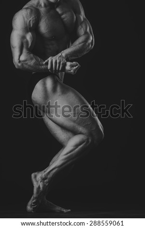 Handsome male bodybuilder. Bodybuilder posing on a black background. Stock Photo. Beautiful muscular body.
