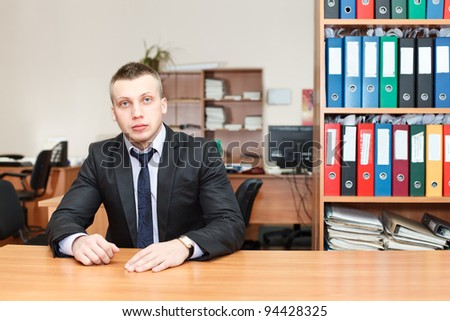 Handsome male business executive sitting behind a bookstand - stock photo