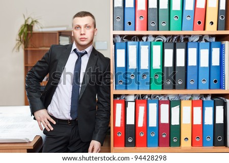 Handsome male business executive standing behind a bookstand - stock photo