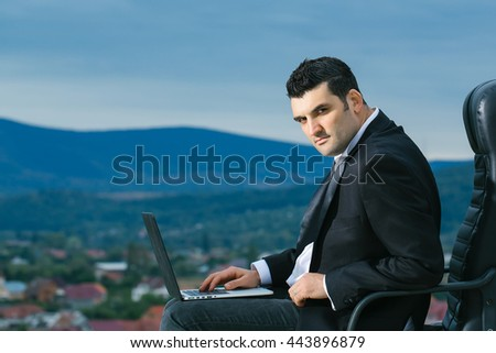 handsome male businessman with courageous face in black formal jacket and white shirt working on laptop sitting on leather office arm chair outdoor on city background