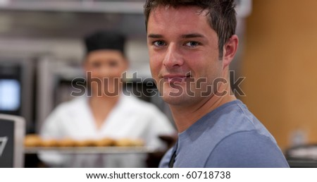 Handsome male customer in a bakery with female baker holding baguettes - stock photo
