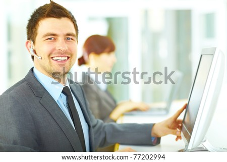 Handsome male customer support operator smiling while posing in office near the computer screen - stock photo