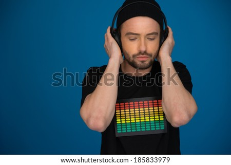 handsome Male DJ with headphones on blue background - stock photo