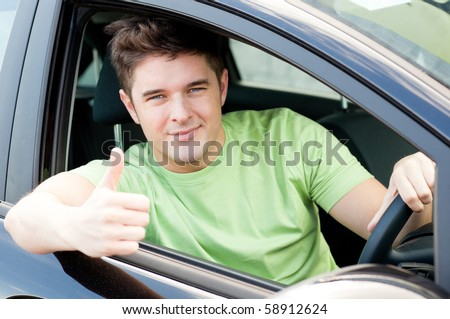 Handsome male driver sitting in a car and smiling - stock photo