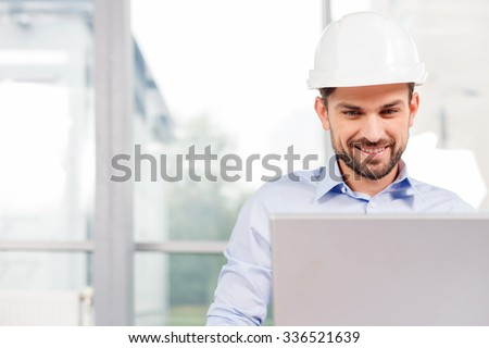 Handsome male engineer is using a notebook for work. He is sitting at the desk and smiling. The man is a white helmet is looking at the screen with aspiration. Copy space in left side - stock photo