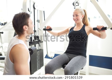 Handsome Male Fitness Trainer Assisting a Young Female Student Doing Exercise on Chest Press Machine Inside the Gym. - stock photo