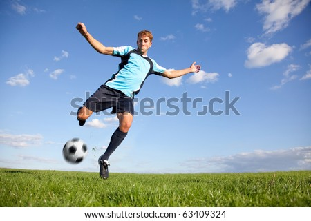 Handsome male football player kicking the ball