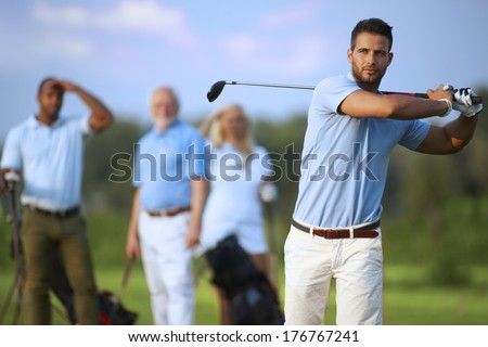 Handsome male golfer swinging golf club, following shot in the air. - stock photo