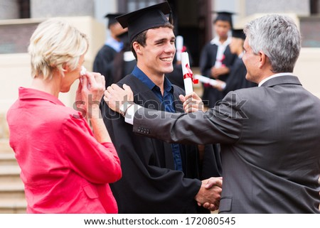 handsome male graduate being congratulated by his father at graduation ceremony - stock photo