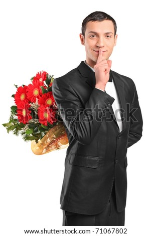 Handsome male hiding a bouquet of flowers and gesturing silence isolated on white background - stock photo