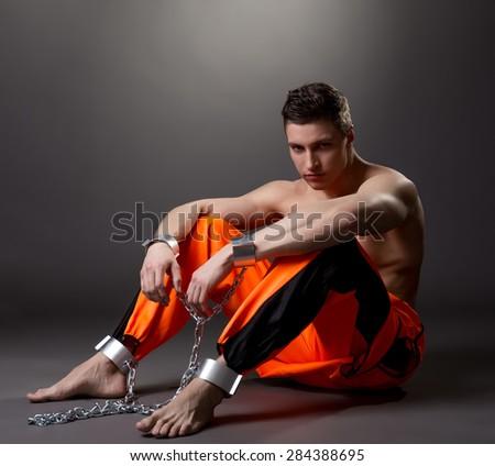 Handsome male model posing as prisoner in studio - stock photo