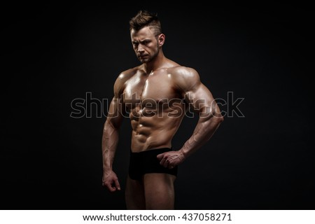 Handsome male model posing at studio in front of a black background. - stock photo