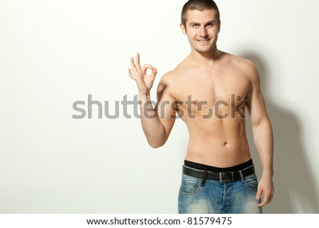 Handsome male model topless showing OK sign, with copy-space - stock photo