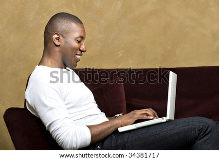 Handsome male model using laptop computer, with copy space.