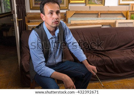 Handsome male painter thinking about his work sitting in his studio or gallery holding  paintbrush - stock photo