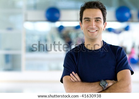Handsome male portait at the gym smiling - stock photo