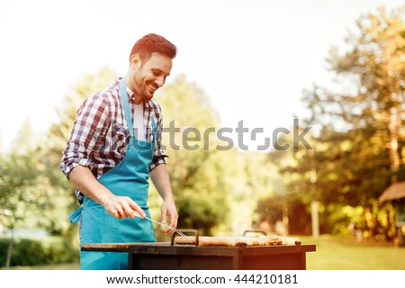 Handsome male prepares barbecue outdoors - stock photo