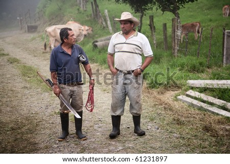 Handsome male ranch hands on dairy farm in Costa Rica - stock photo