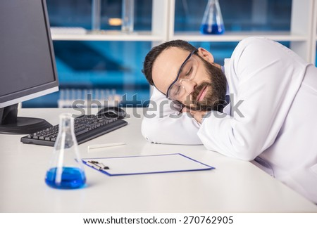 Handsome male scientist sleeping in safety glasses at his workplace in a laboratory.