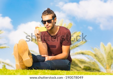 Handsome male sitting in the park using a cellphone - stock photo