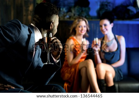 Handsome male staring at attractive young girls in night club. - stock photo
