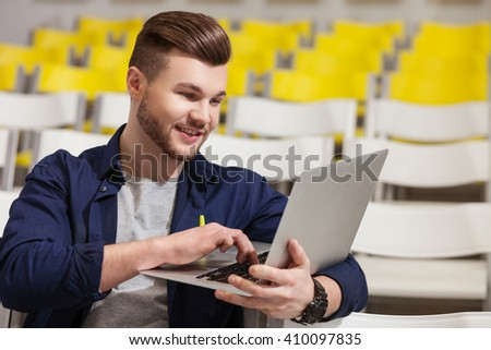 Handsome male student is studying with laptop