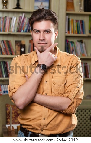 handsome male teacher \ student in a library - stock photo