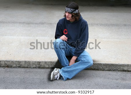 Handsome male teenager sitting on concrete listening to music. - stock photo
