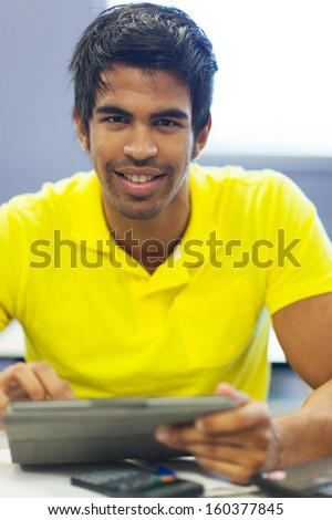handsome male university student using tablet compute in lecture room - stock photo
