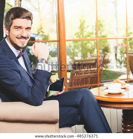 Handsome male using mobile phone, has a french breakfast at cafe restaurant. Smiling businessman. Elegant successful man