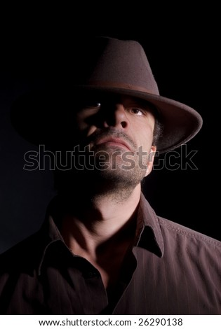 Handsome male wearing a hat; has a somewhat arrogant/intimidating look - stock photo