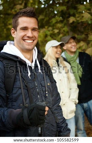 Handsome man and friends hiking in autumn forest, smiling, looking at camera. - stock photo