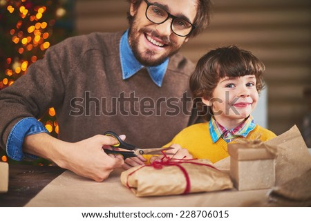 Handsome man and his son looking at camera while packing xmas gifts - stock photo