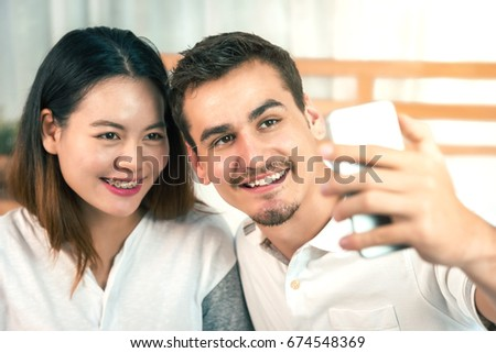 Handsome Man and His Wife are Making Selfie in Bedroom - Warm Family Concept