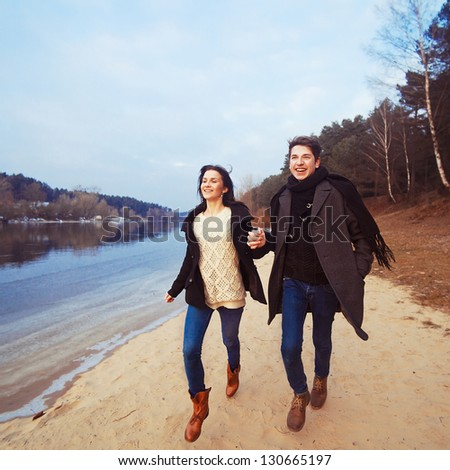 Handsome man and pretty woman having fun on the beach. Young couple running and smiling in spring