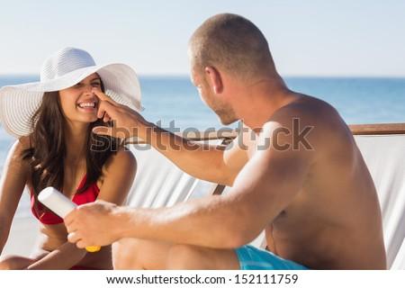 Handsome man applying sun cream on his girlfriends nose on the beach - stock photo