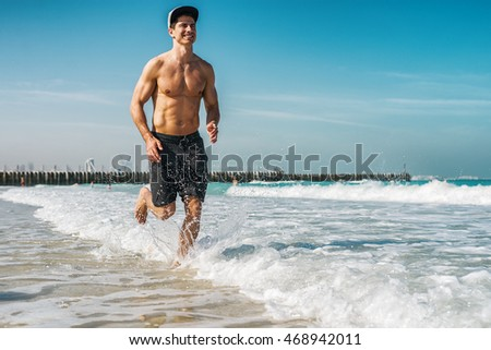 Handsome man at the beach, running through the water.