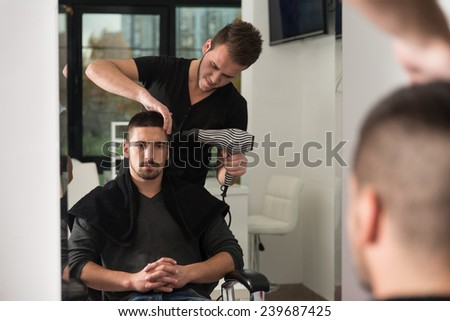 Handsome Man At The Hairdresser Blow Drying His Hair - stock photo