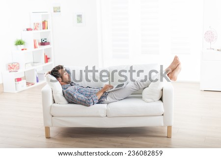 handsome man barefoot lying comfortably on a white couch and using a laptop - stock photo